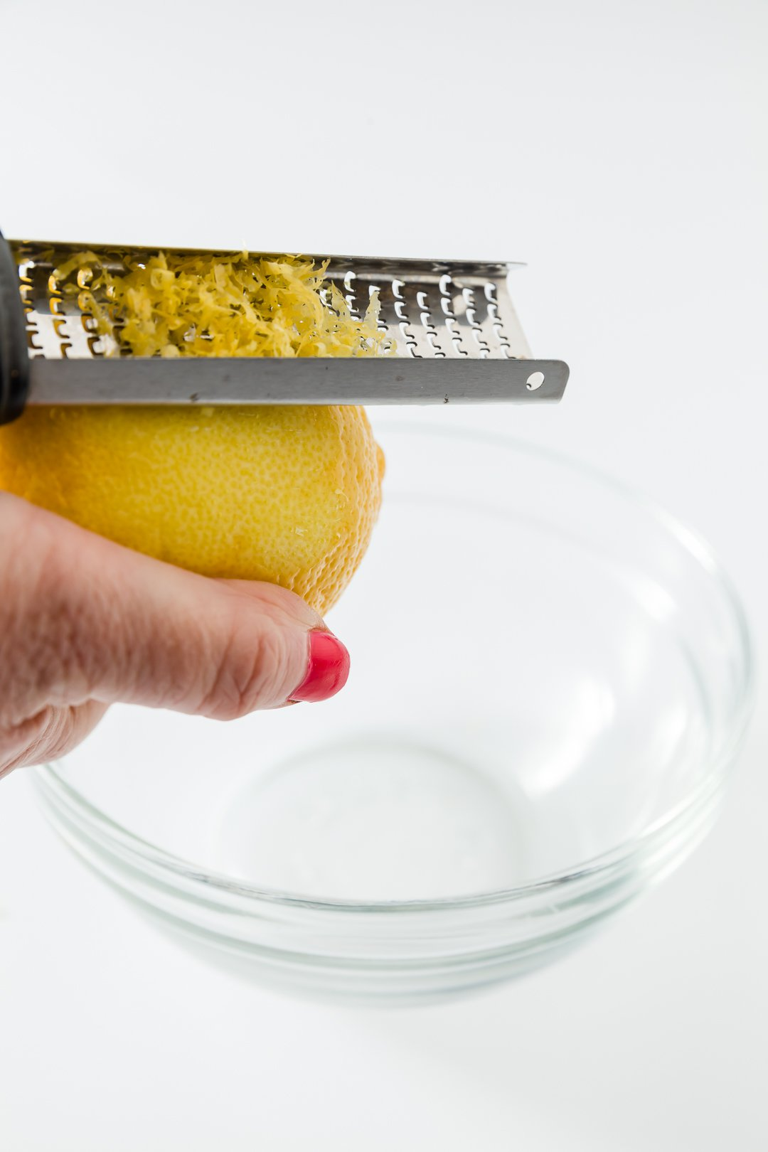 zesting a lemon with a microplane zester into a glass bowl