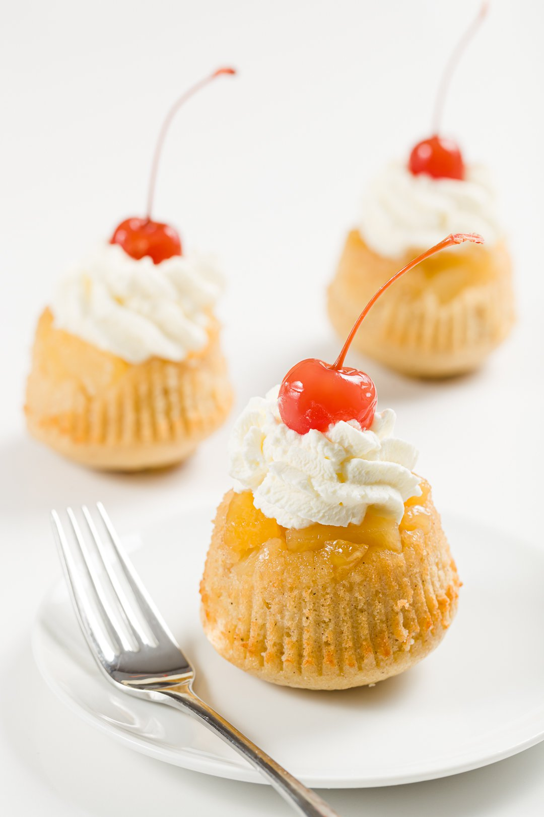 pineapple upside-down cupcakes topped with whipped cream and maraschino cherries
