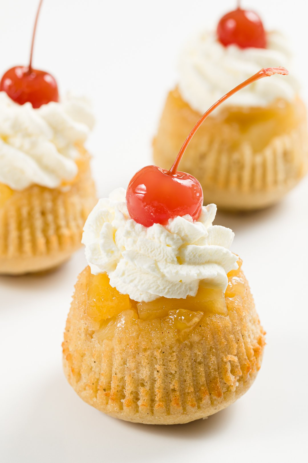 close-up view of a pineapple upside-down cupcake topped with whipped cream and a maraschino cherry