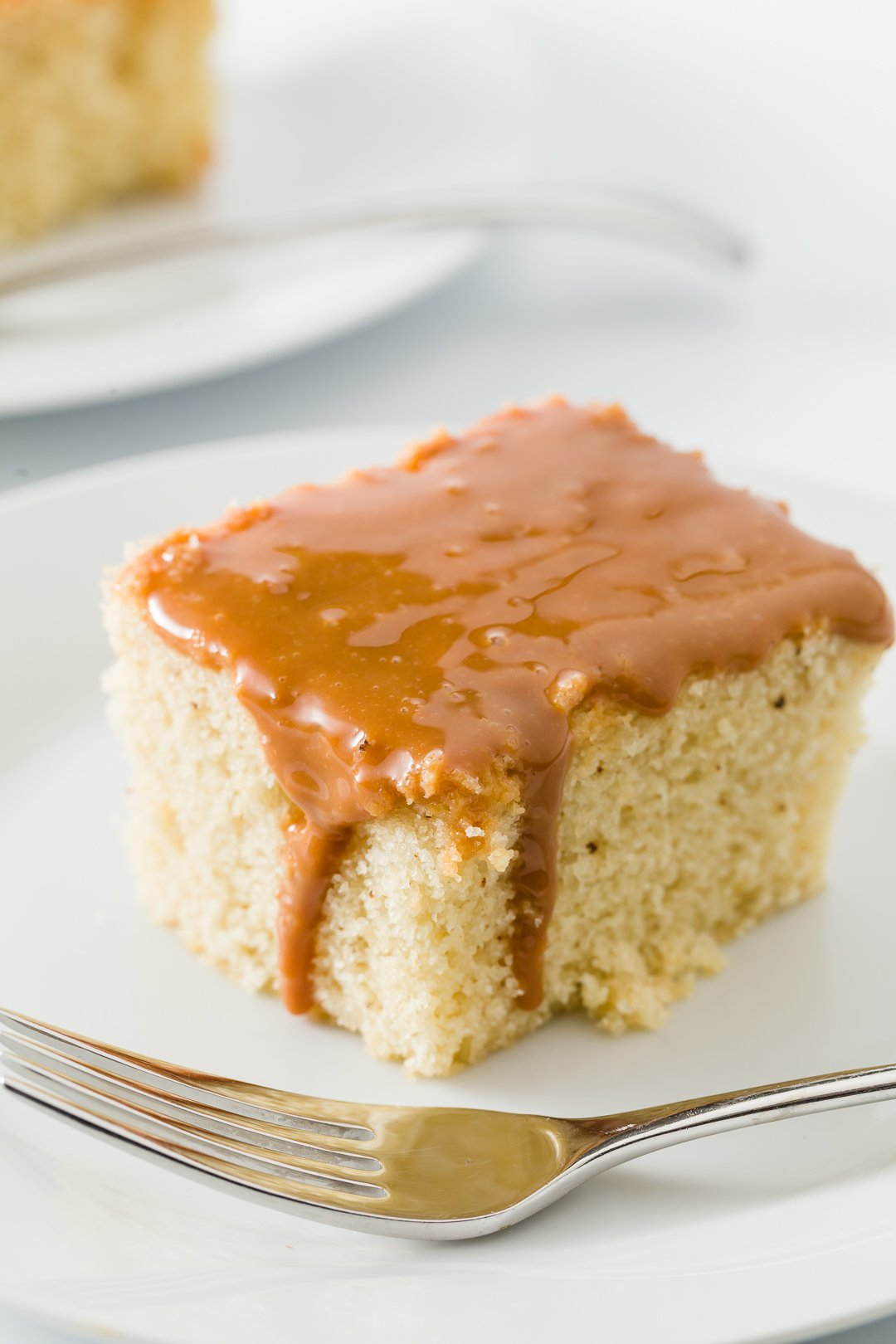 Slice of Dulce de leche cake on a plate with dulce de leche dripping down the side