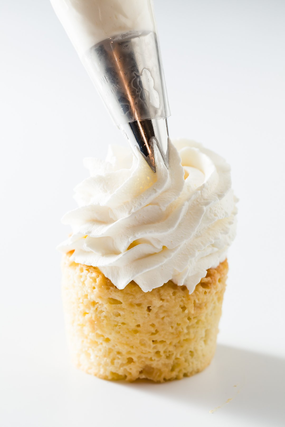 Topping tres leches cupcakes with whipped cream