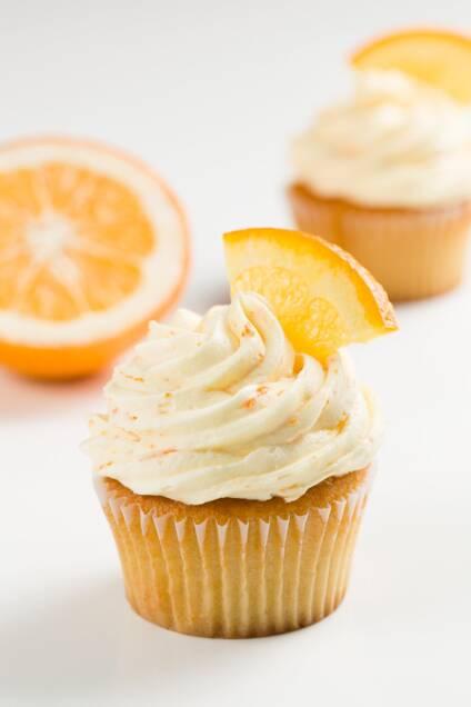 Orange frosting on vanilla cupcakes