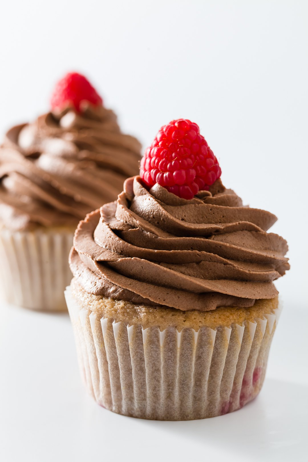Two raspberry cupcakes frosted with chocolate whipped cream and topped with fresh raspberries