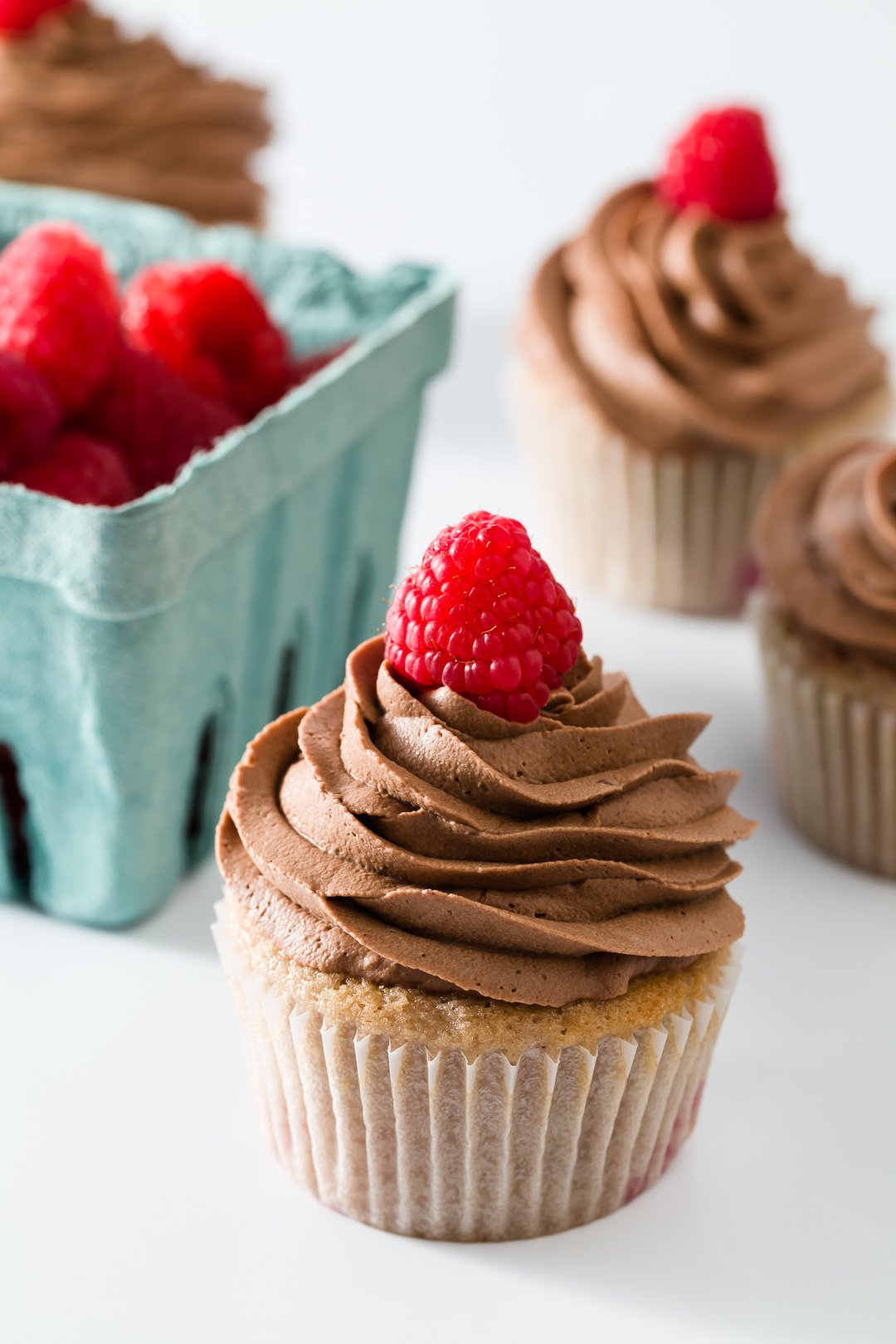 Raspberry cupcakes with raspberries in the background