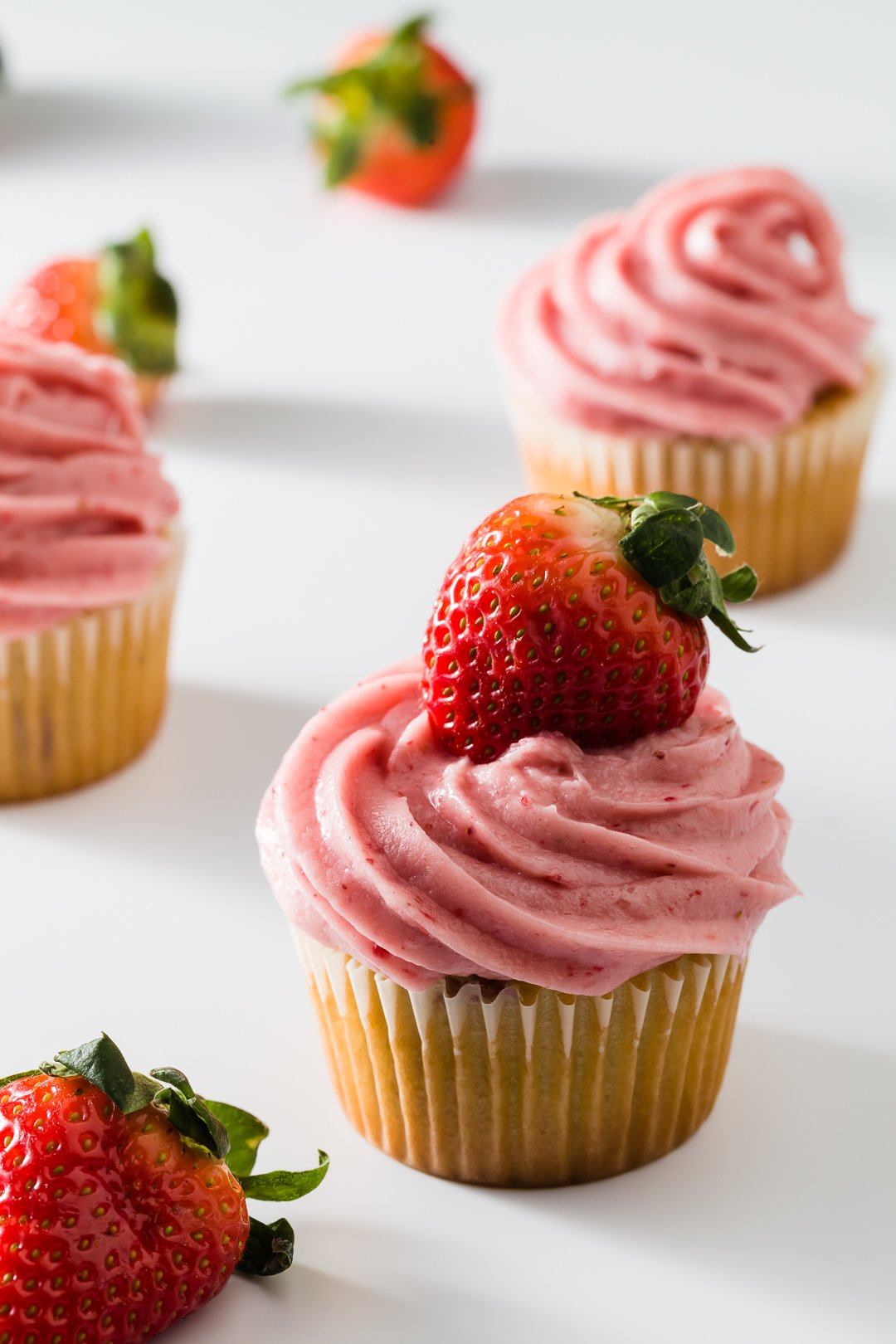 A group of cupcakes on white topped with strawberry cream cheese frosting topped with a fresh strawberry