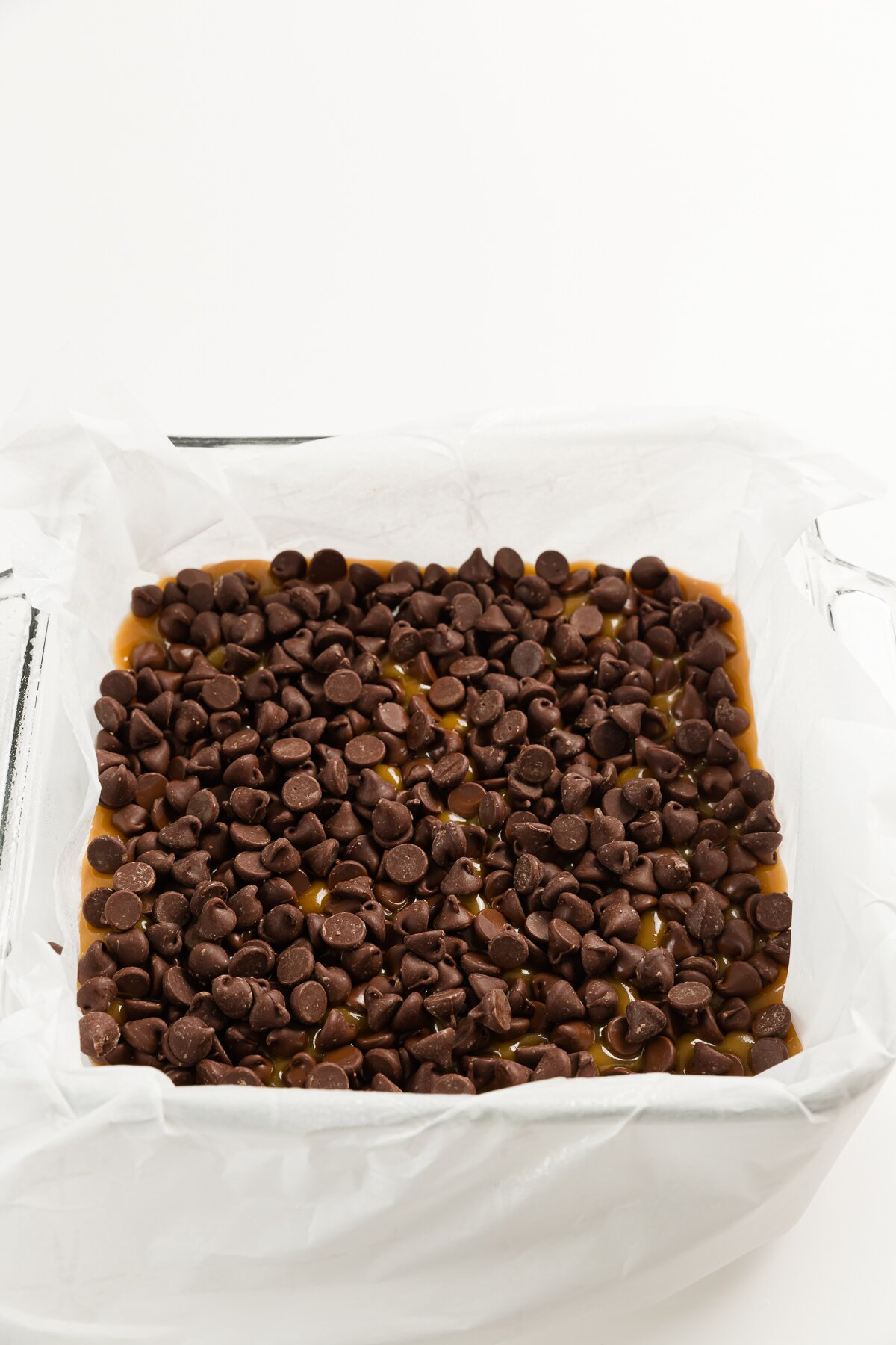 Top down of square dish filled with chocolate chips over toffee