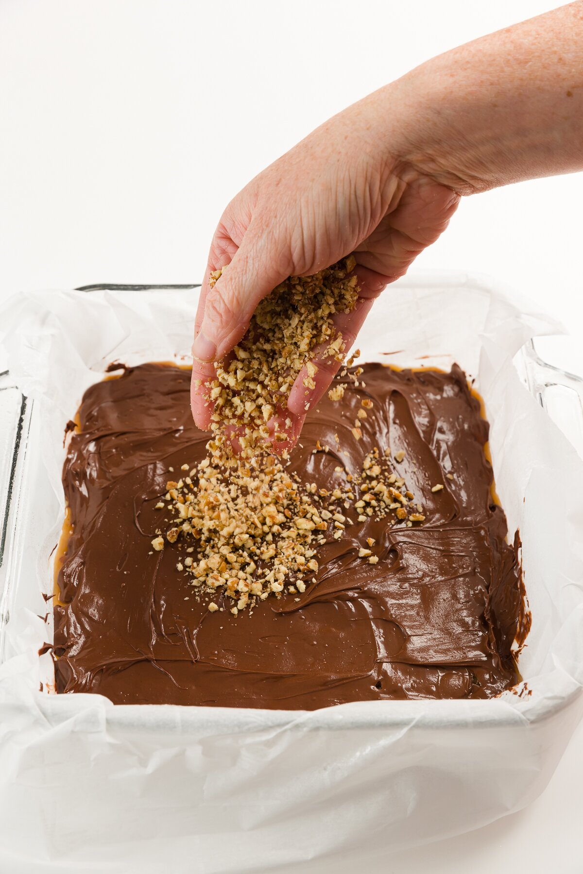 Sprinkling nuts over melted chocolate in square baking dish