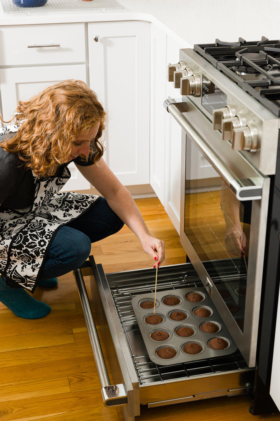Pulling chocolate cupcakes from the oven