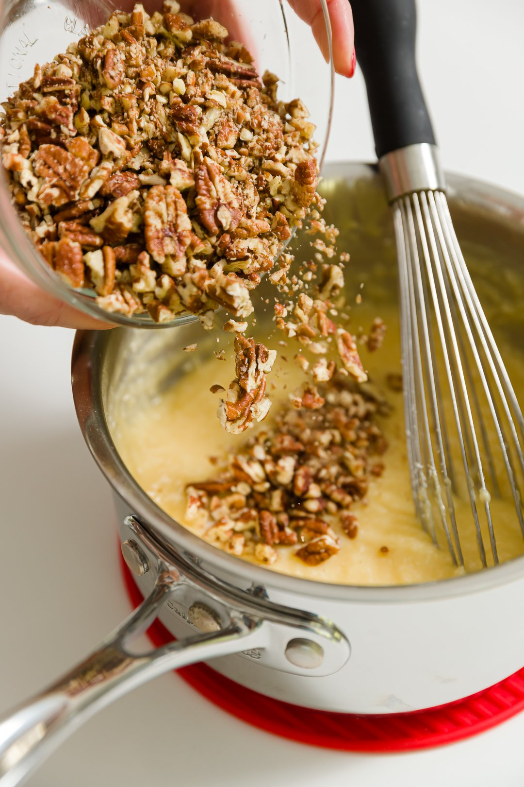 Adding chopped pecans to pot