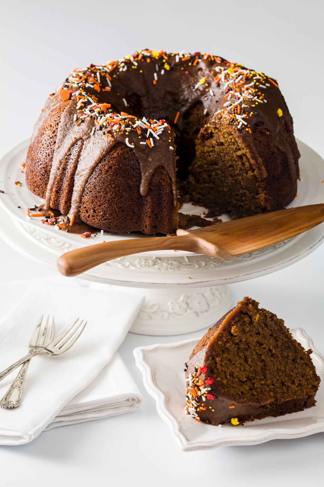 pumpkin Bundt cake sitting on a cake stand with a slice removed in the foreground