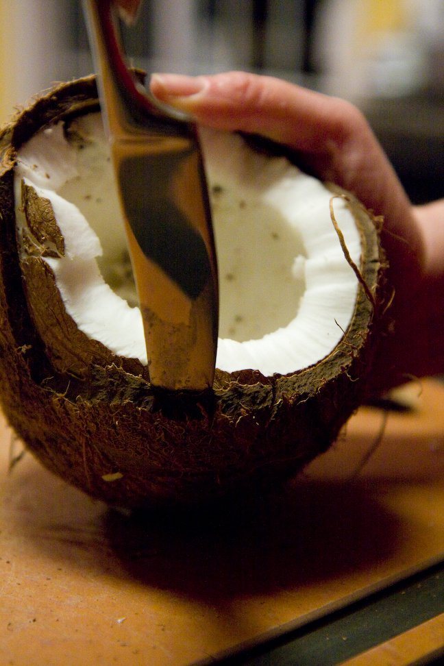 Cutting open a coconut to make desiccated coconut