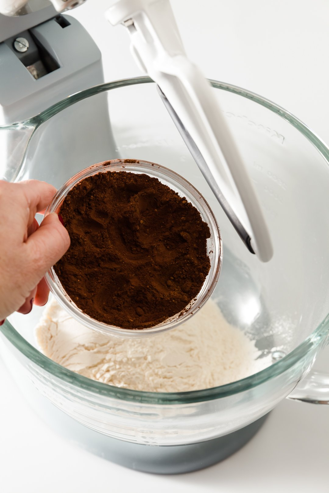Dark cocoa powder being adding to a mixing bowl