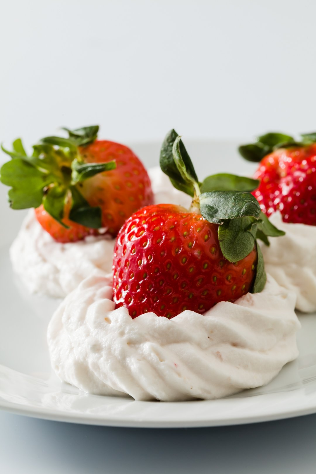 fresh strawberries sitting on top of fresh whipped cream