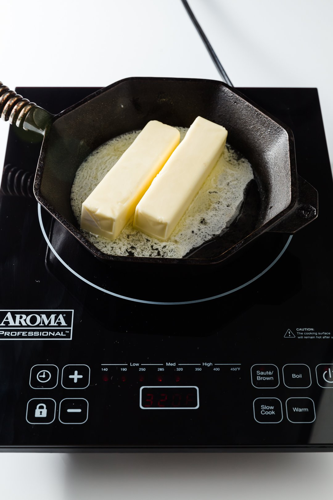 Two sticks of butter starting to melt on a skillet