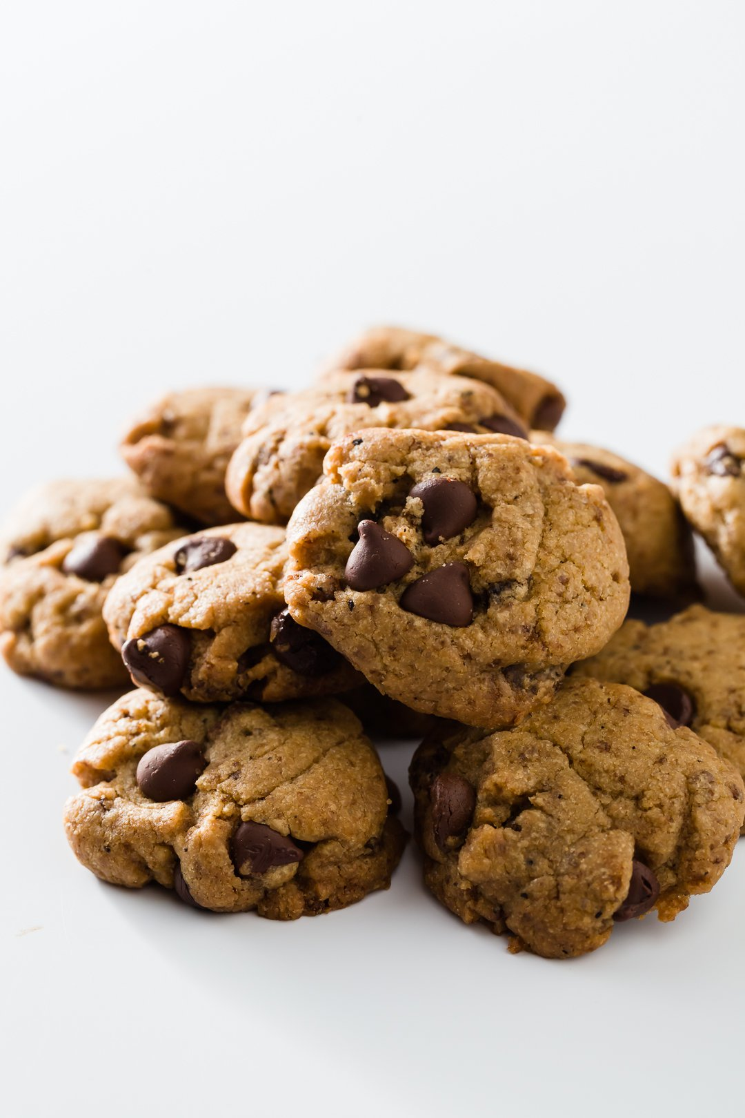 Pile of brown butter chocolate chip cookies on white background