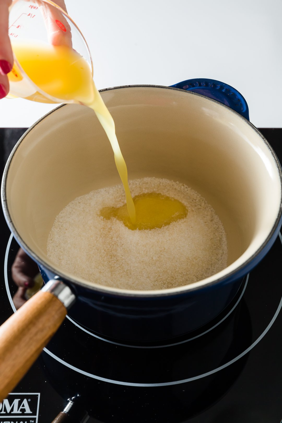 Orange juice and sugar in a pot