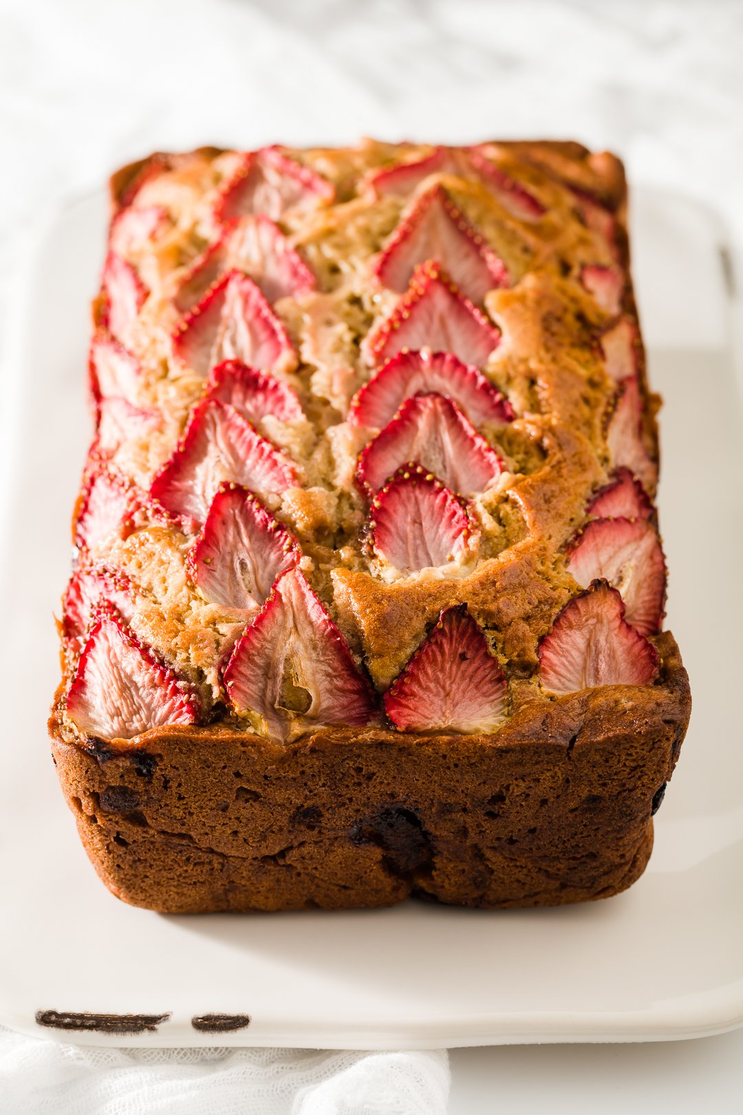 Unsliced loaf of strawberry banana bread