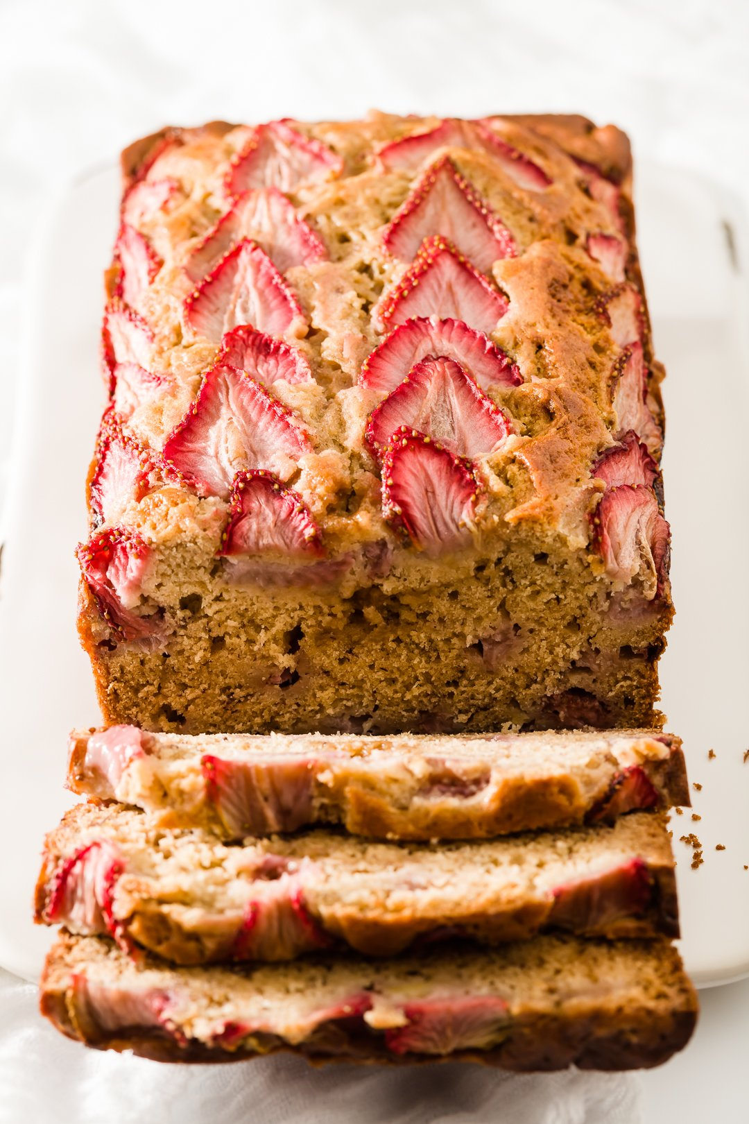 A load of strawberry banana bread with three slices falling down from it