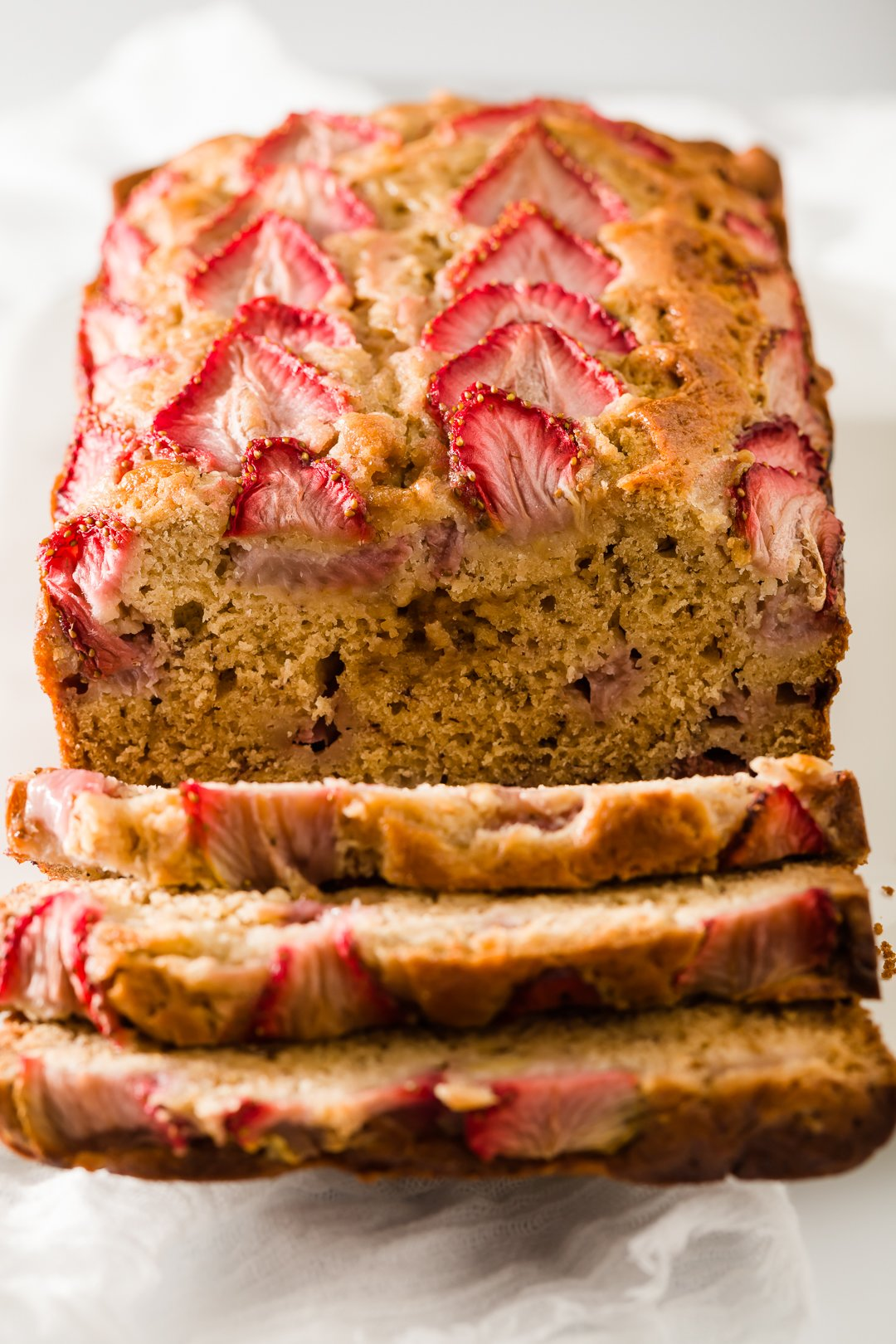 Strawberry banana bread with three slices falling down from it