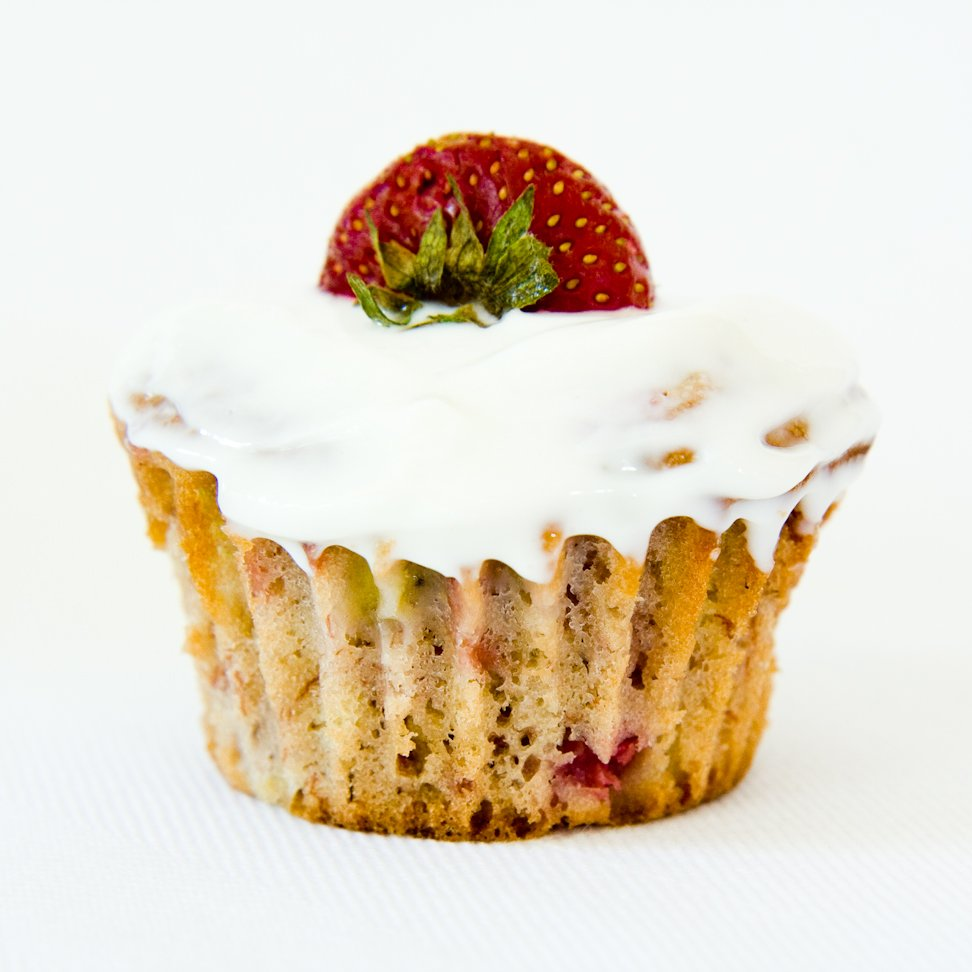 a strawberry banana cupcake with no cupcake liner topped with a strawberry