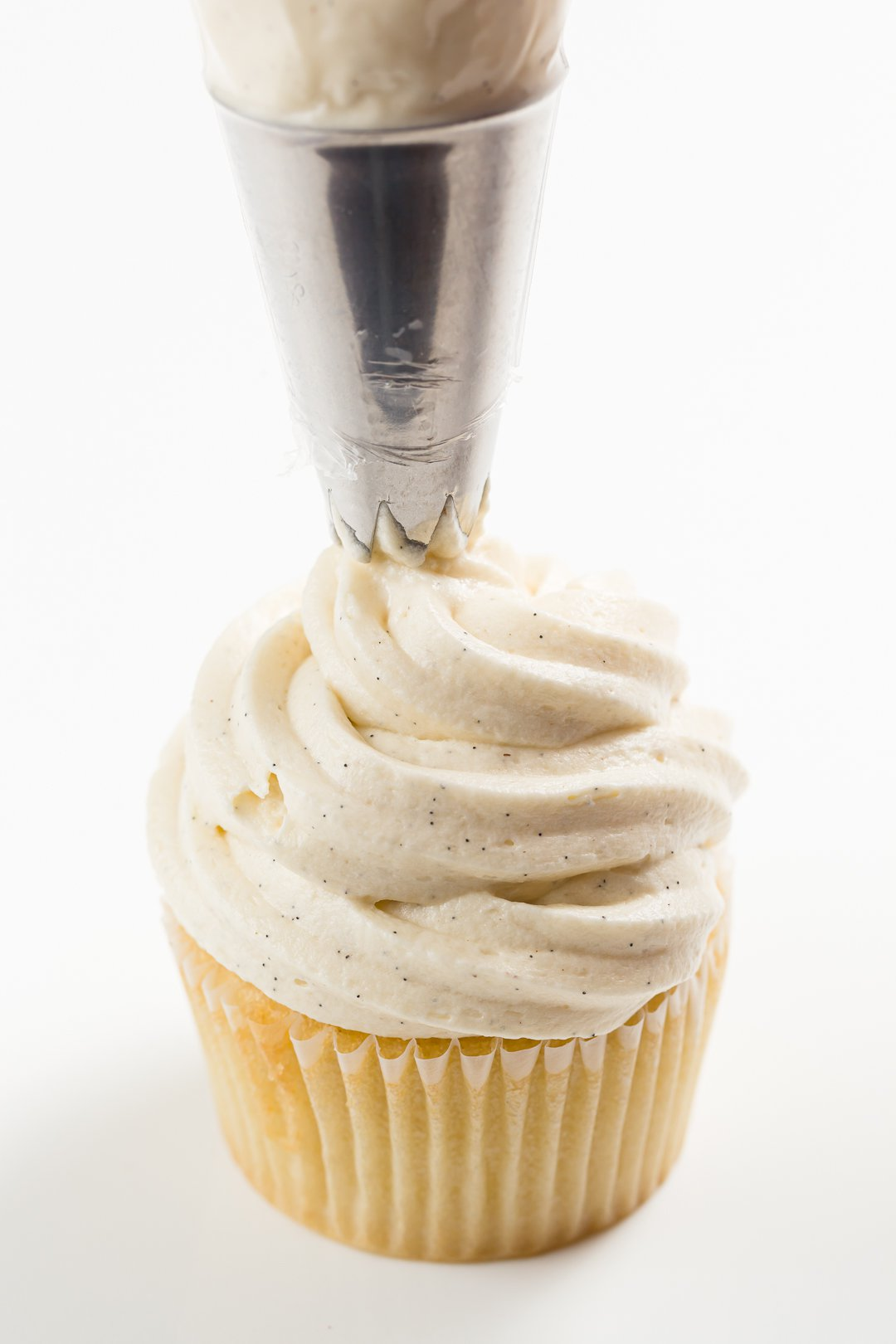 Piping sour cream frosting on a cupcake