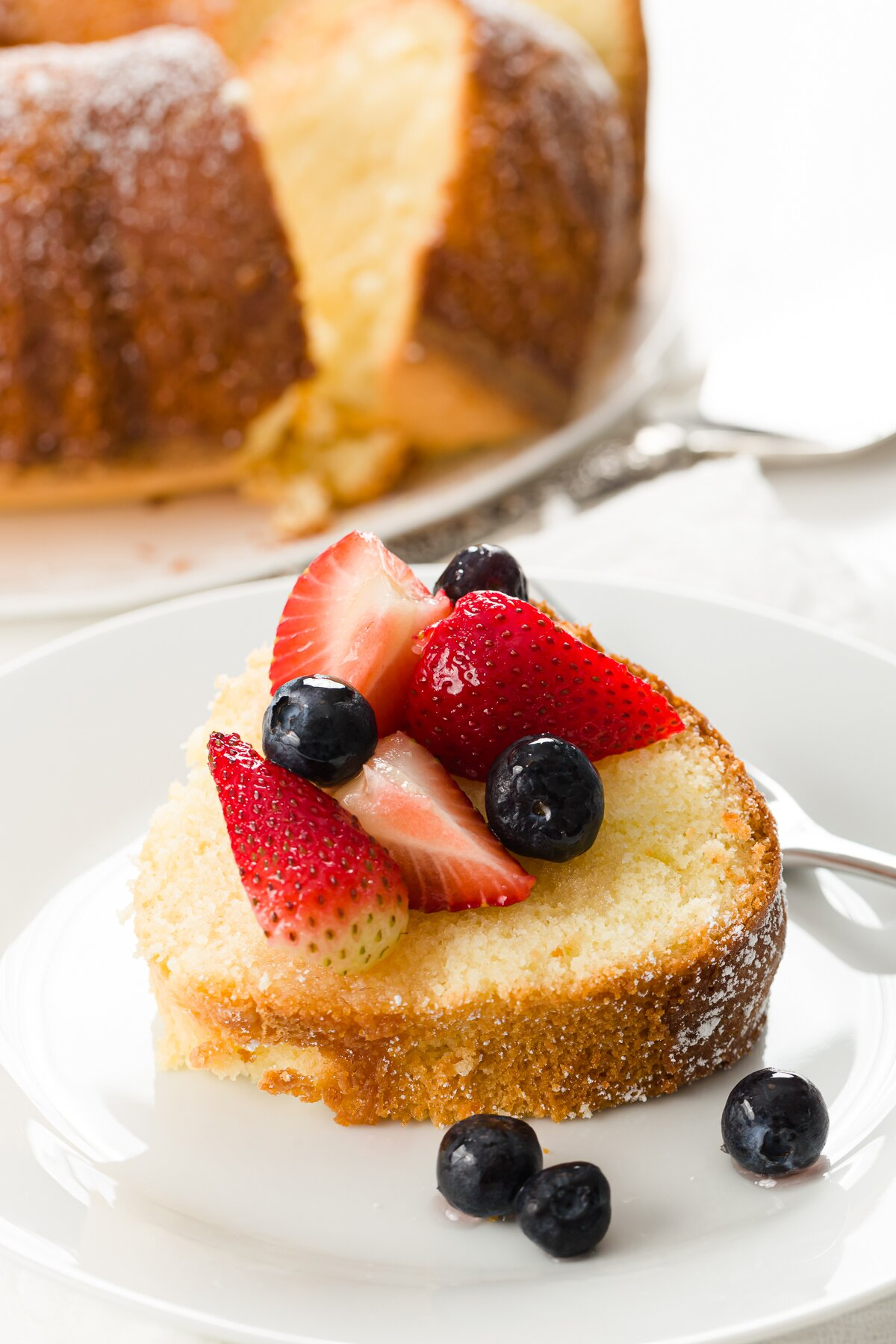 a slice of pound cake covered in berries with the full cake in the background