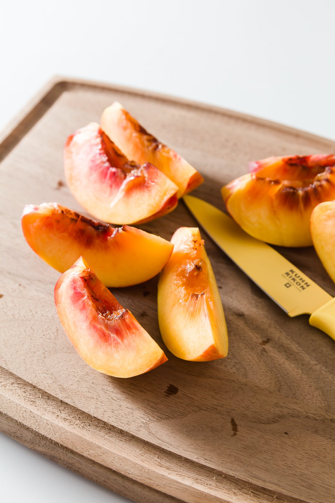 a cutting board with sliced peaches and a knife