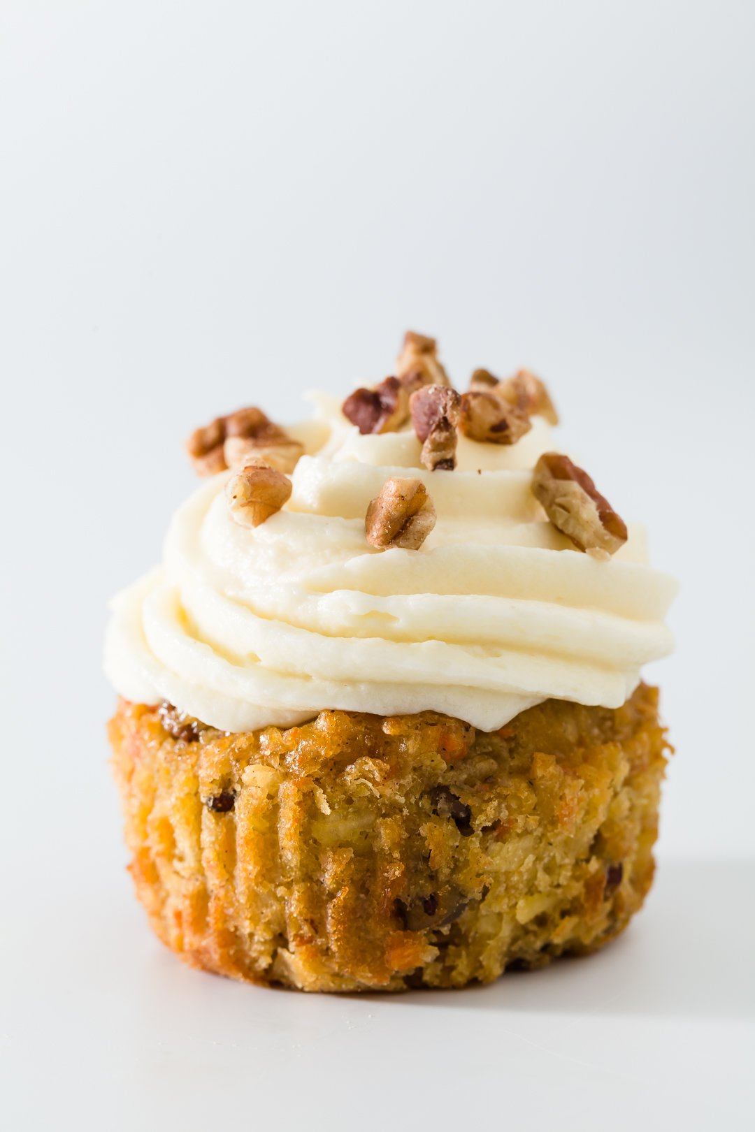 Carrot Cake Cupcakes topped with chopped pecans