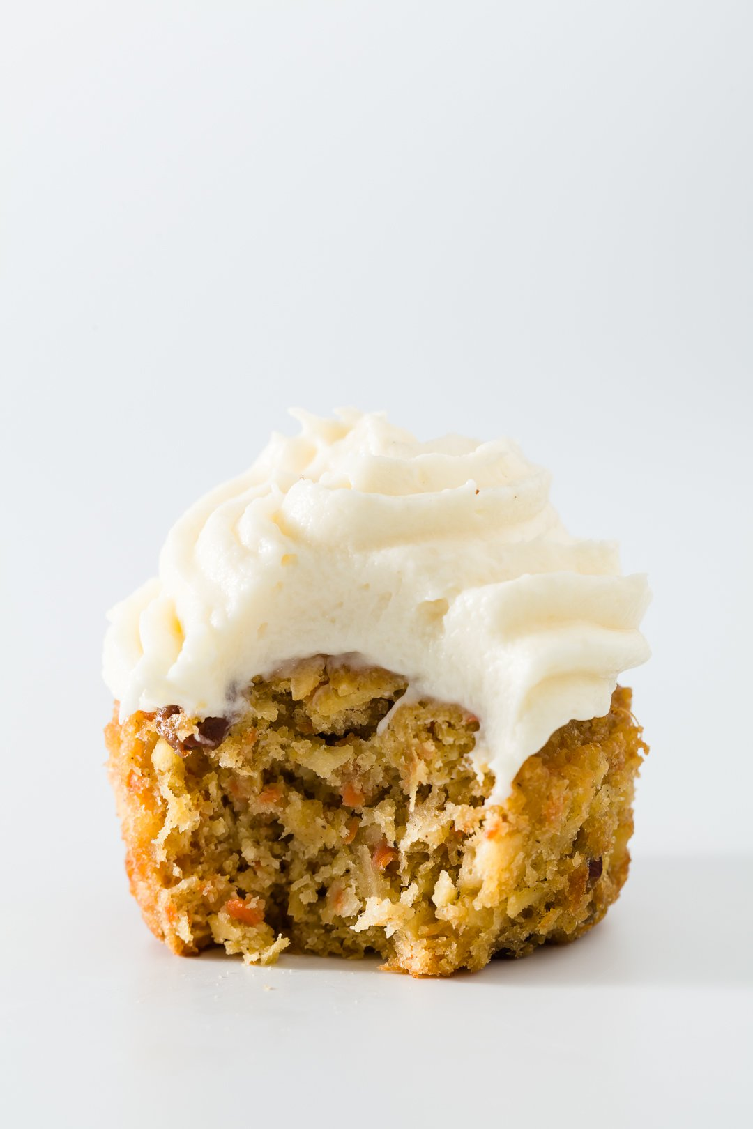 One carrot cake cupcake with a bite taken out of it