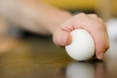 An egg being cracked on flat surface