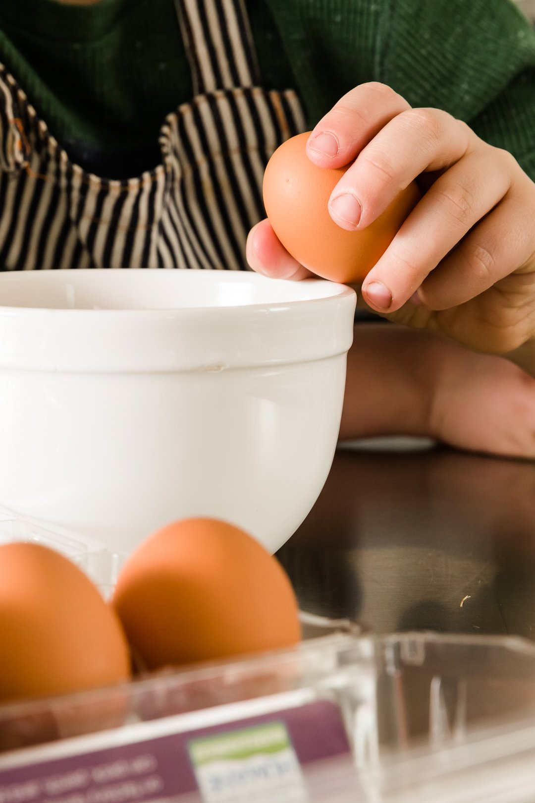 Myles cracking an egg on the edge of a bowl
