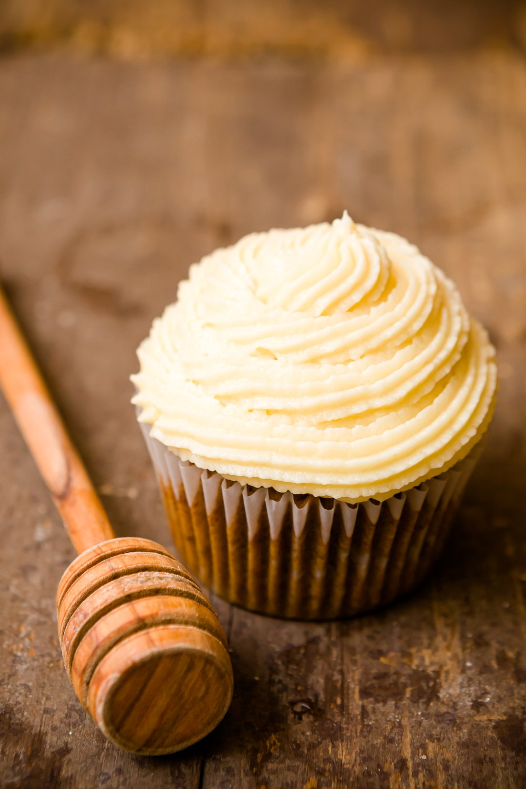 Honey cupcake with a honey dipper next to it