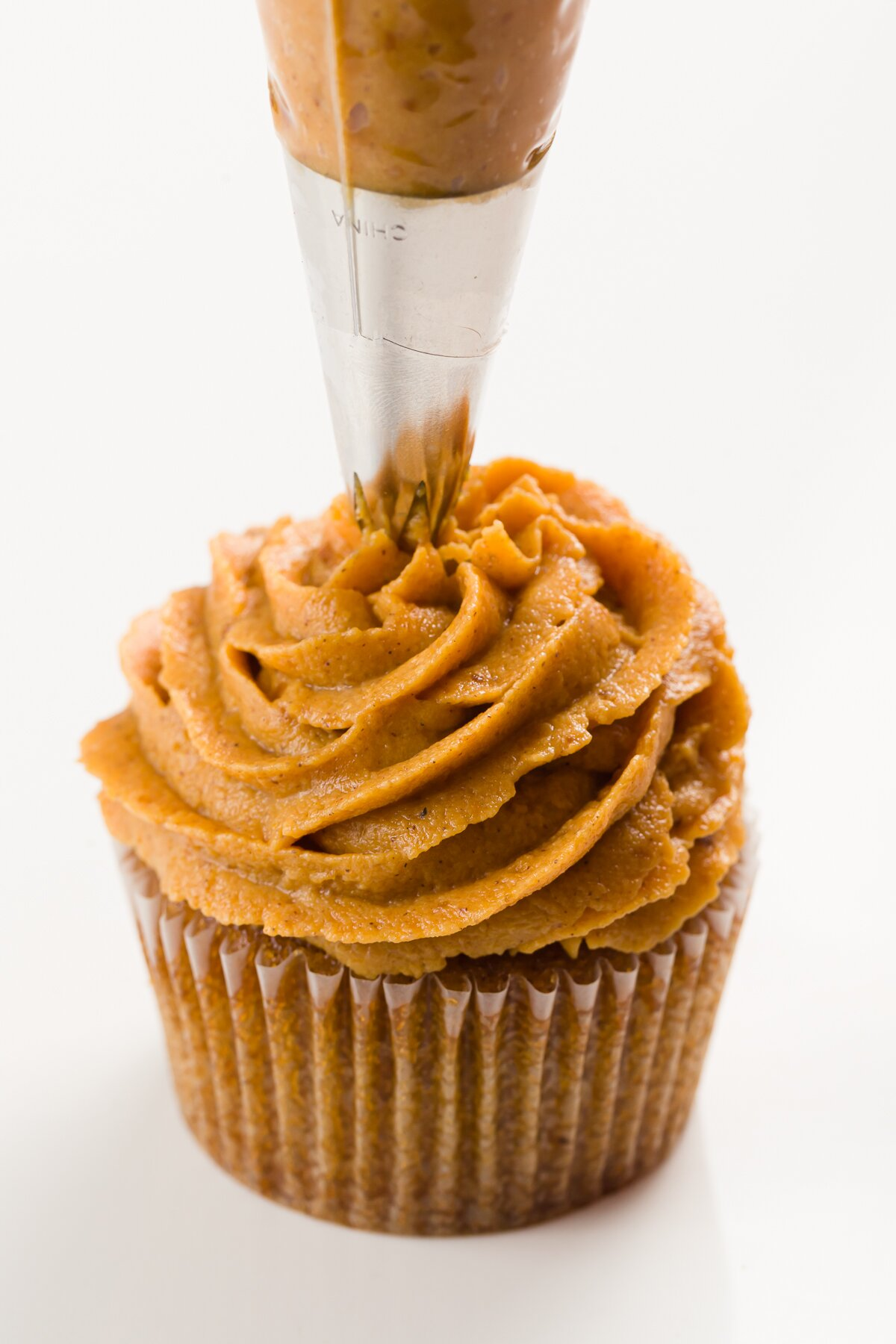Piping pumpkin frosting onto a cupcake