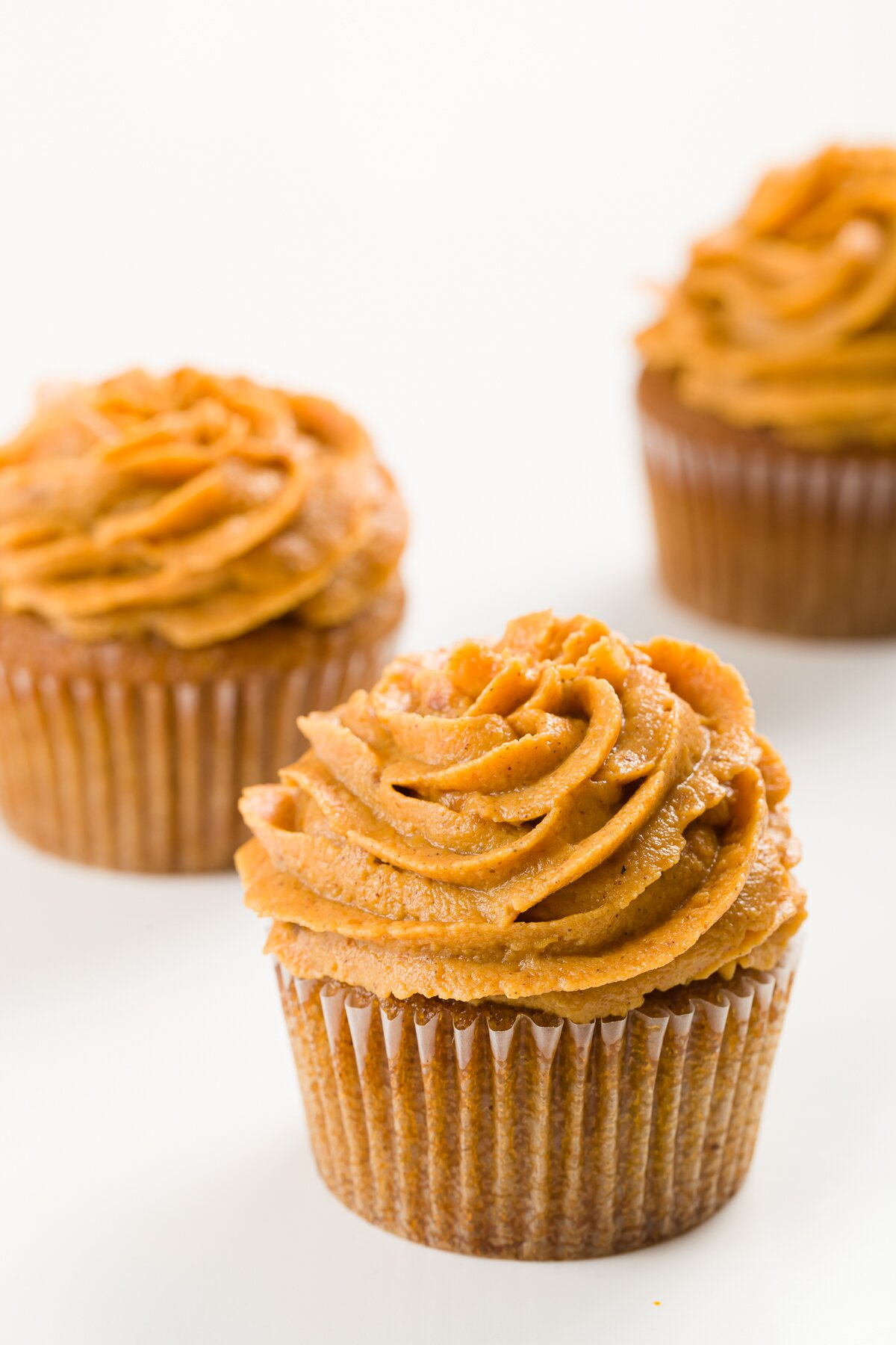 Three cupcakes on a white background frosted with pumpkin frosting