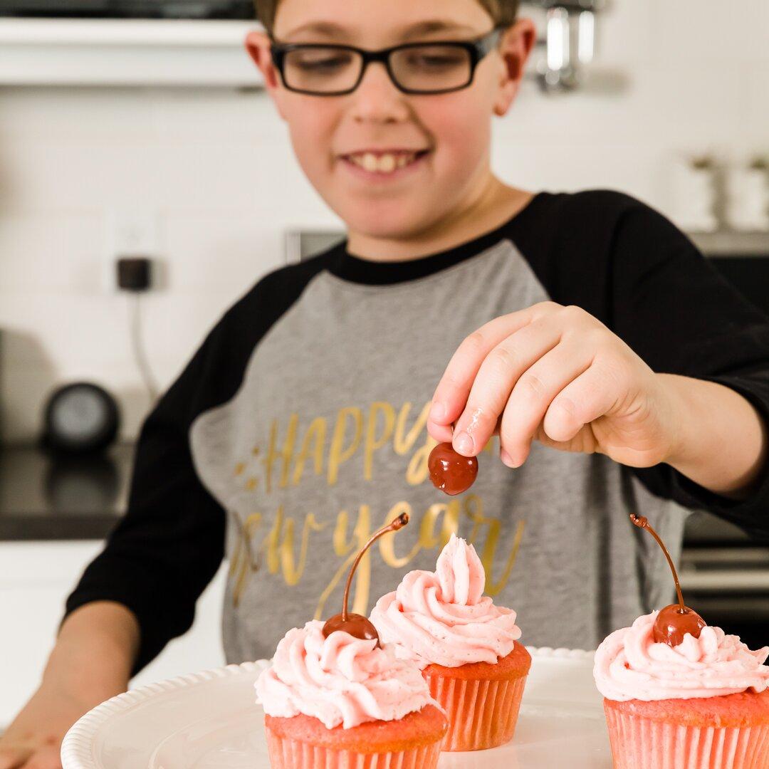 Myles agregando una cereza a un pastelito