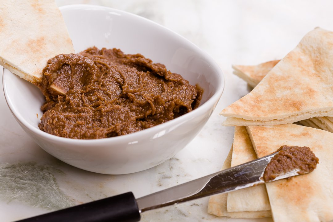 Chocolate hummus in a bowl with fresh pita bread nearby