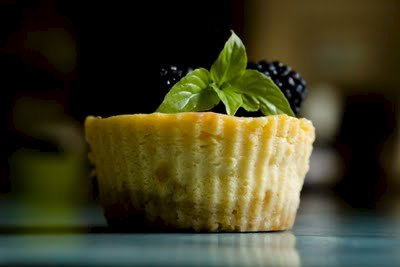 Side view of a lemon icebox jumbo cupcake garnished with blackberries and lemon basil, showing the shortbread crust