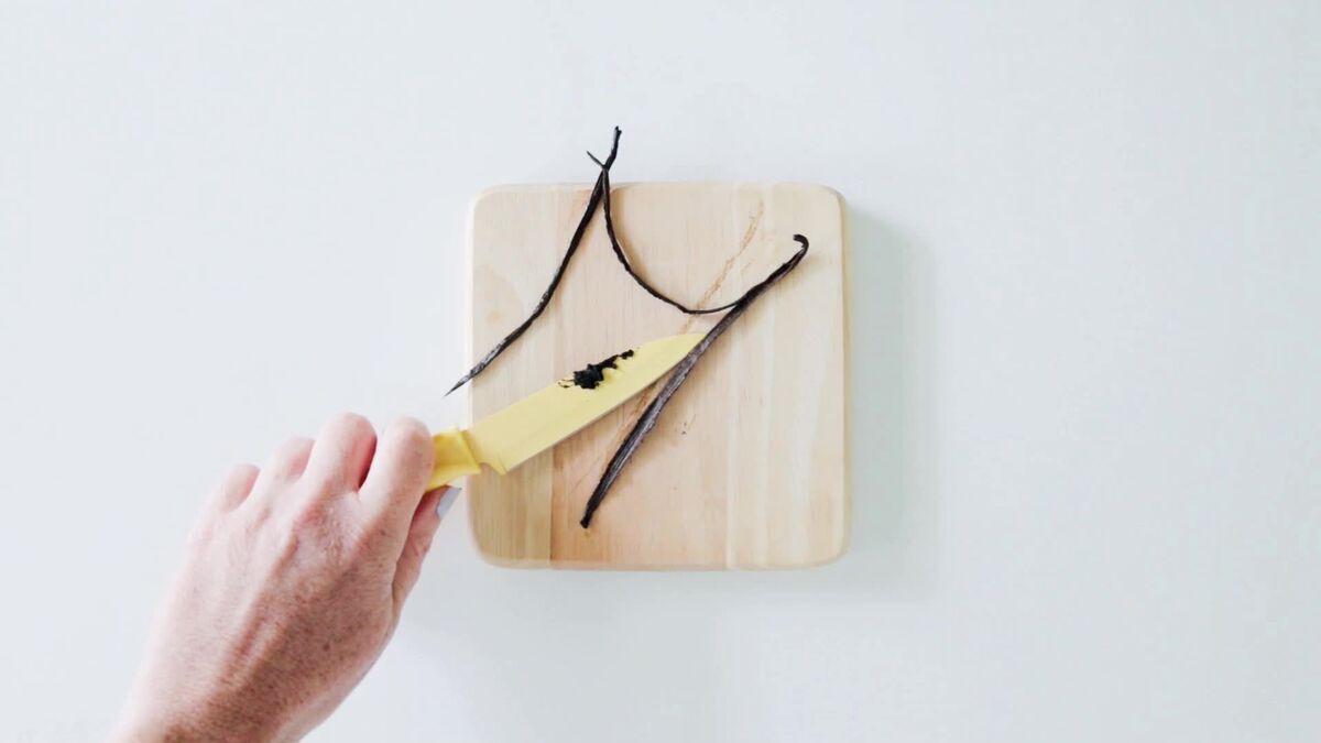 Scraping a vanilla bean on a cutting board to make vanilla sugar