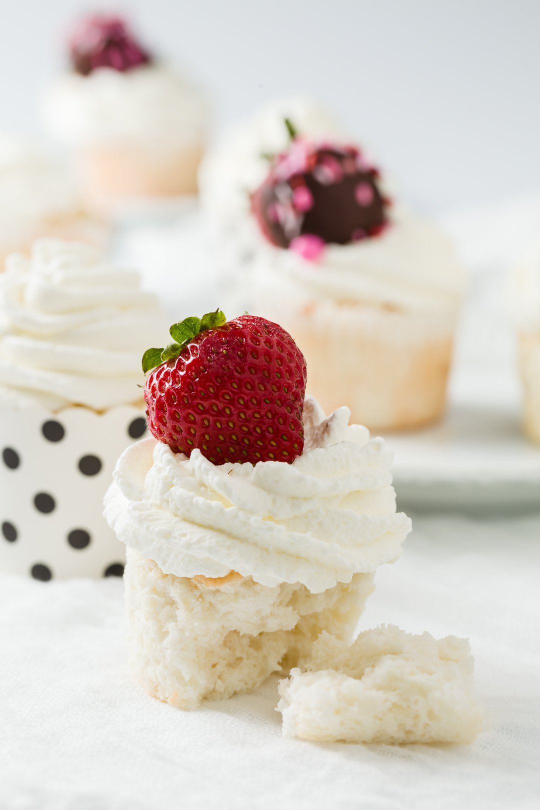 a grouping of angel food cupcakes topped with strawberries