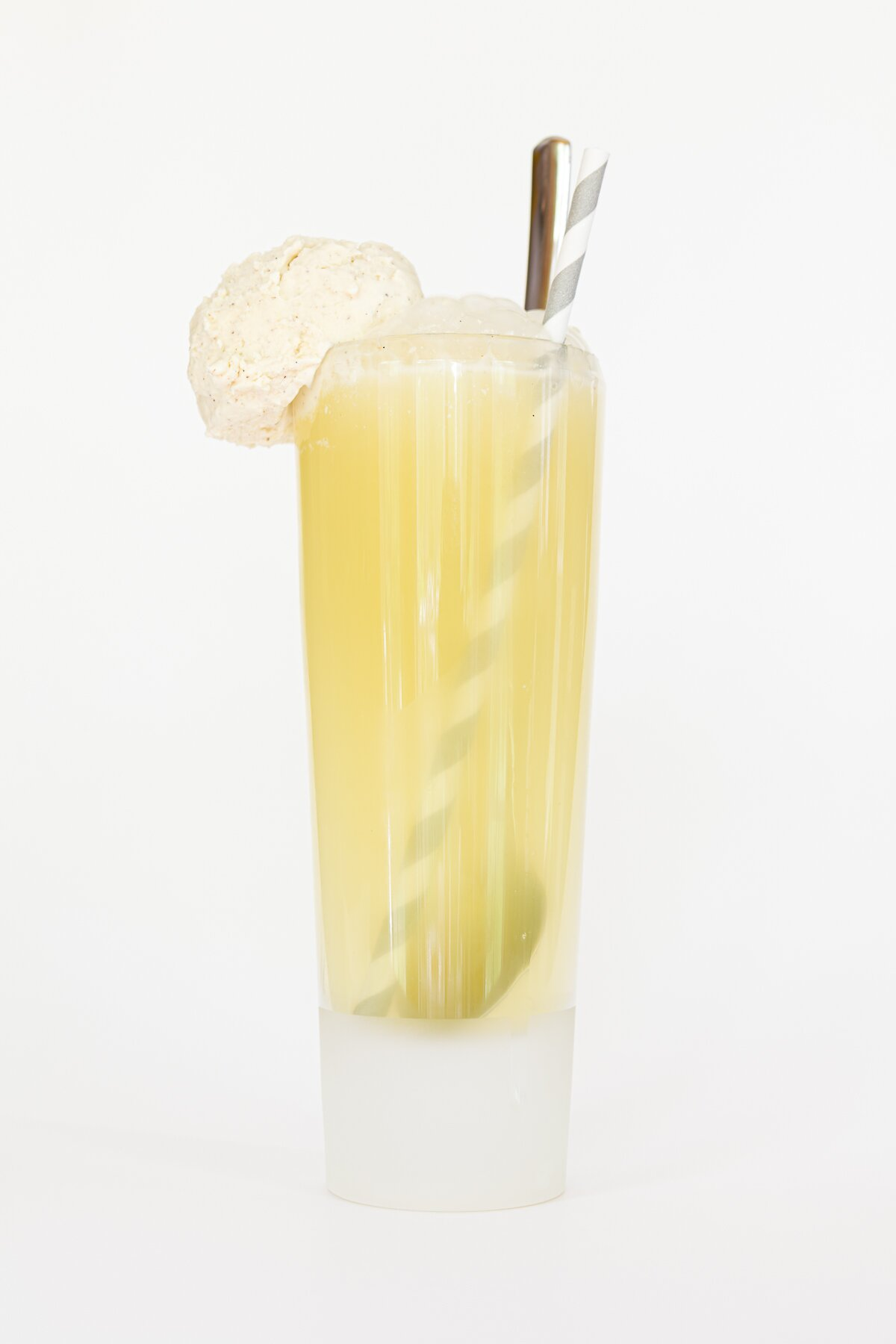 head-on view of a limoncello float in a tall glass with ice cream on the rim, served with a spoon and paper straw