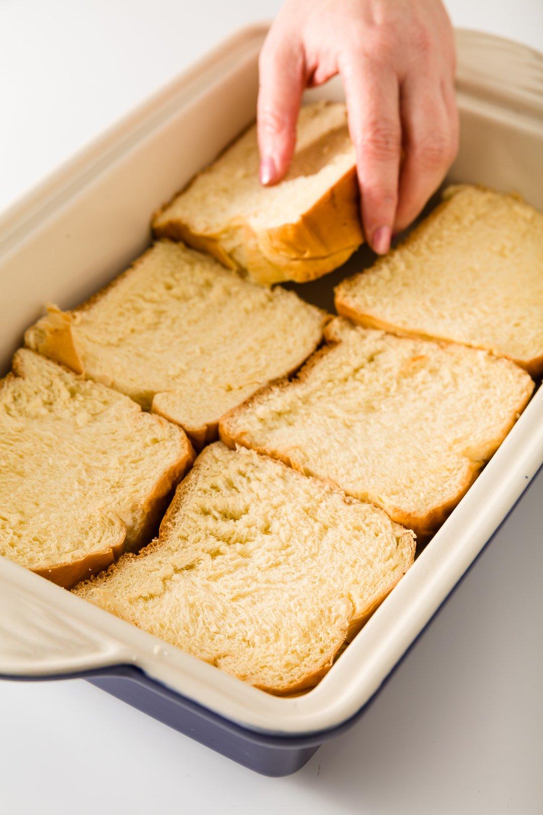 lining a casserole dish with brioche bread