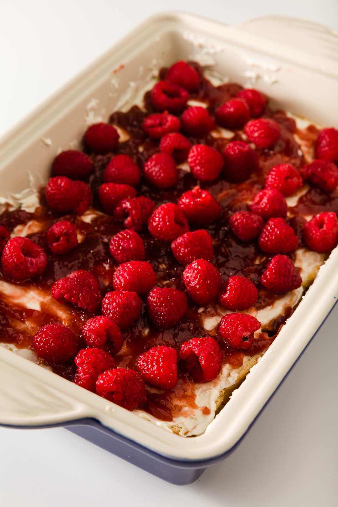 cream cheese, raspberry jam, and raspberries on top of bread in casserole dish