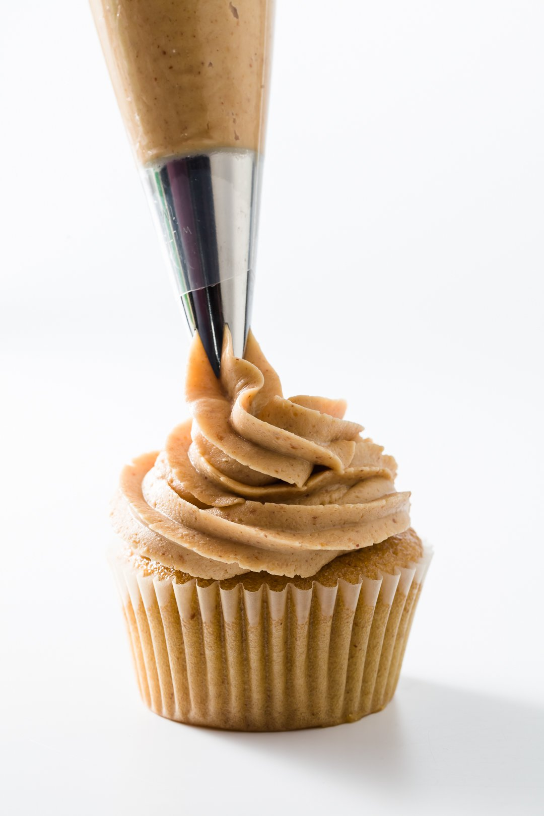 Peanut butter frosting being piped onto cupcakes