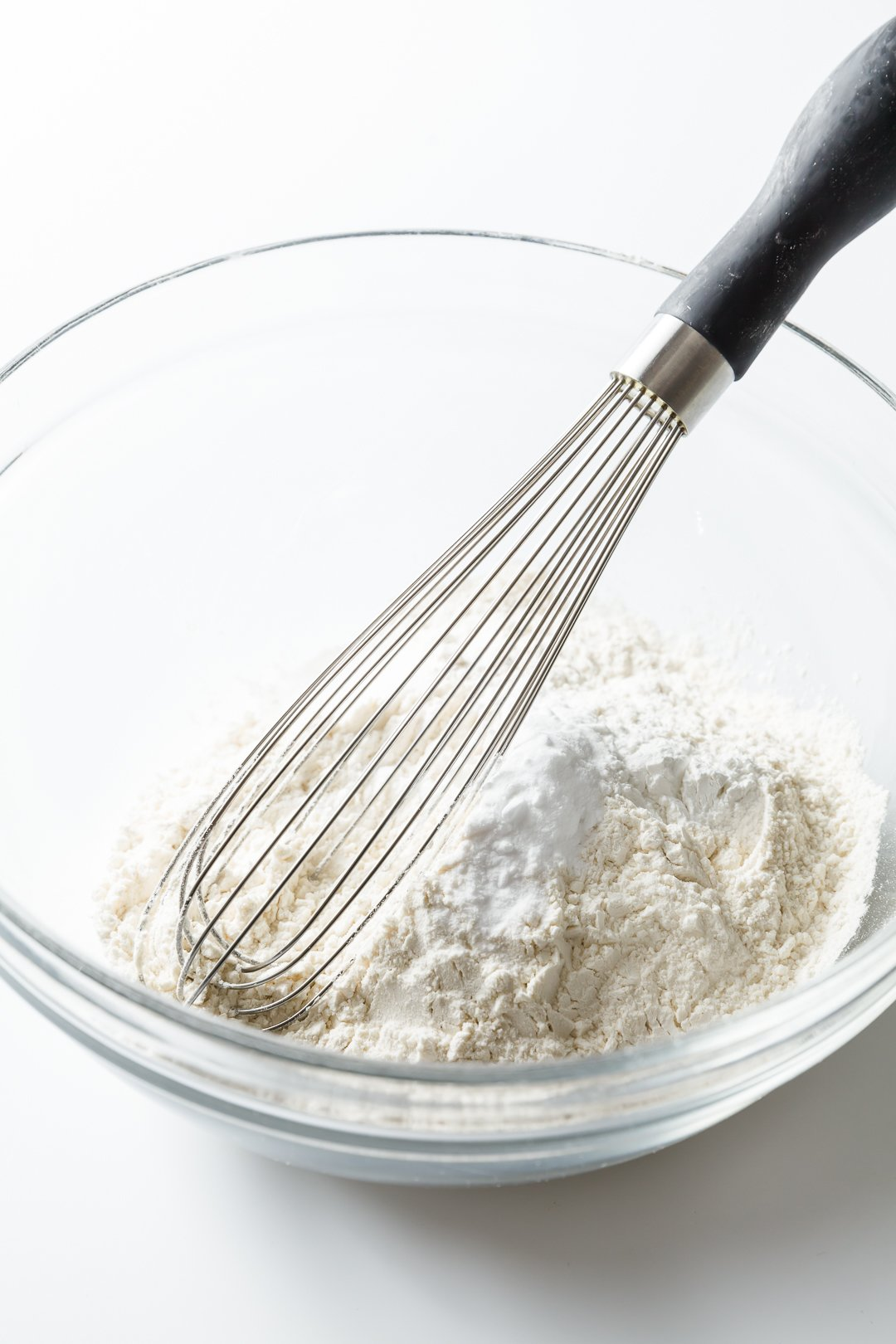 Whisking dry ingredients together in a glass bowl