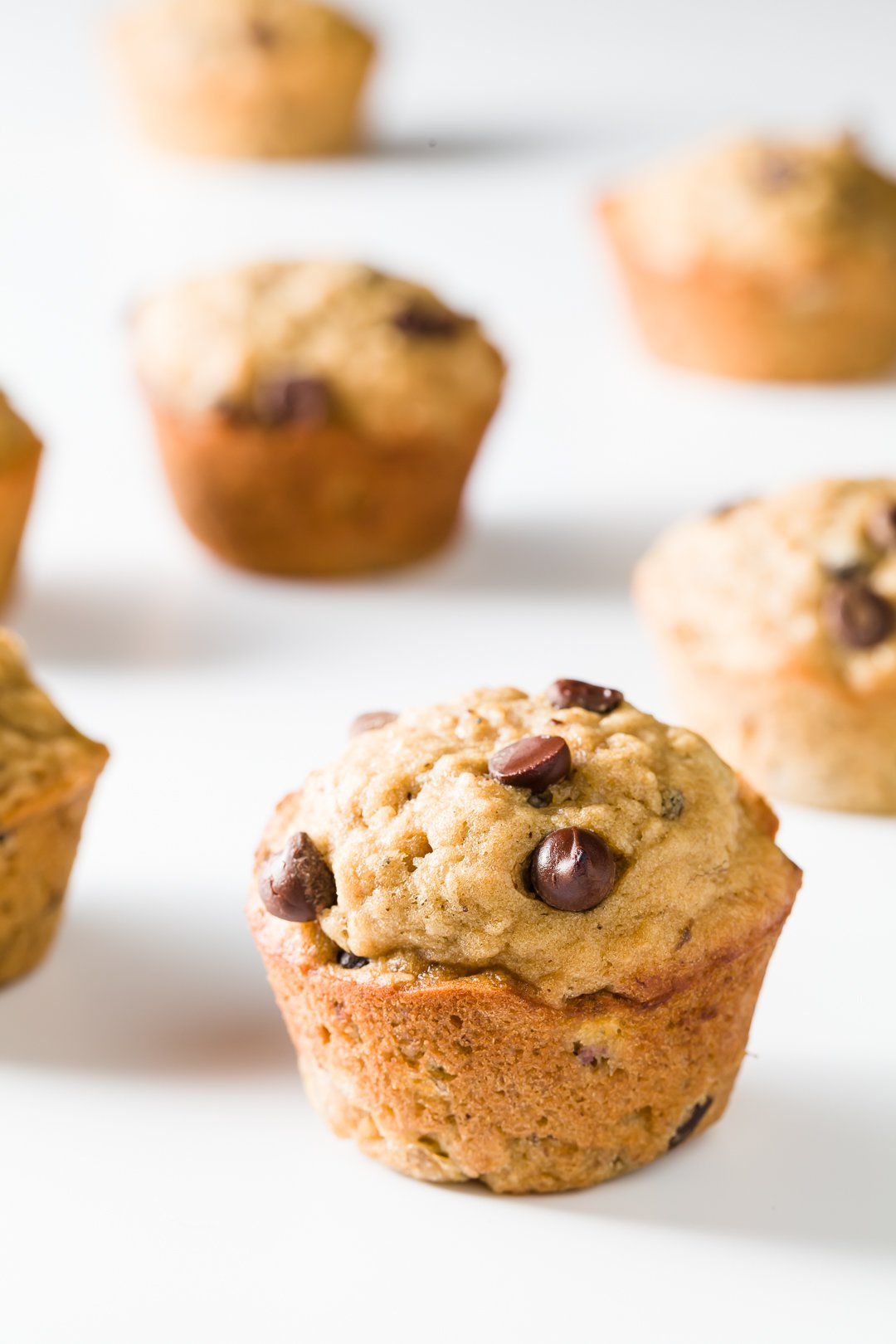 Banana oatmeal chocolate chip muffins scattered on a white background