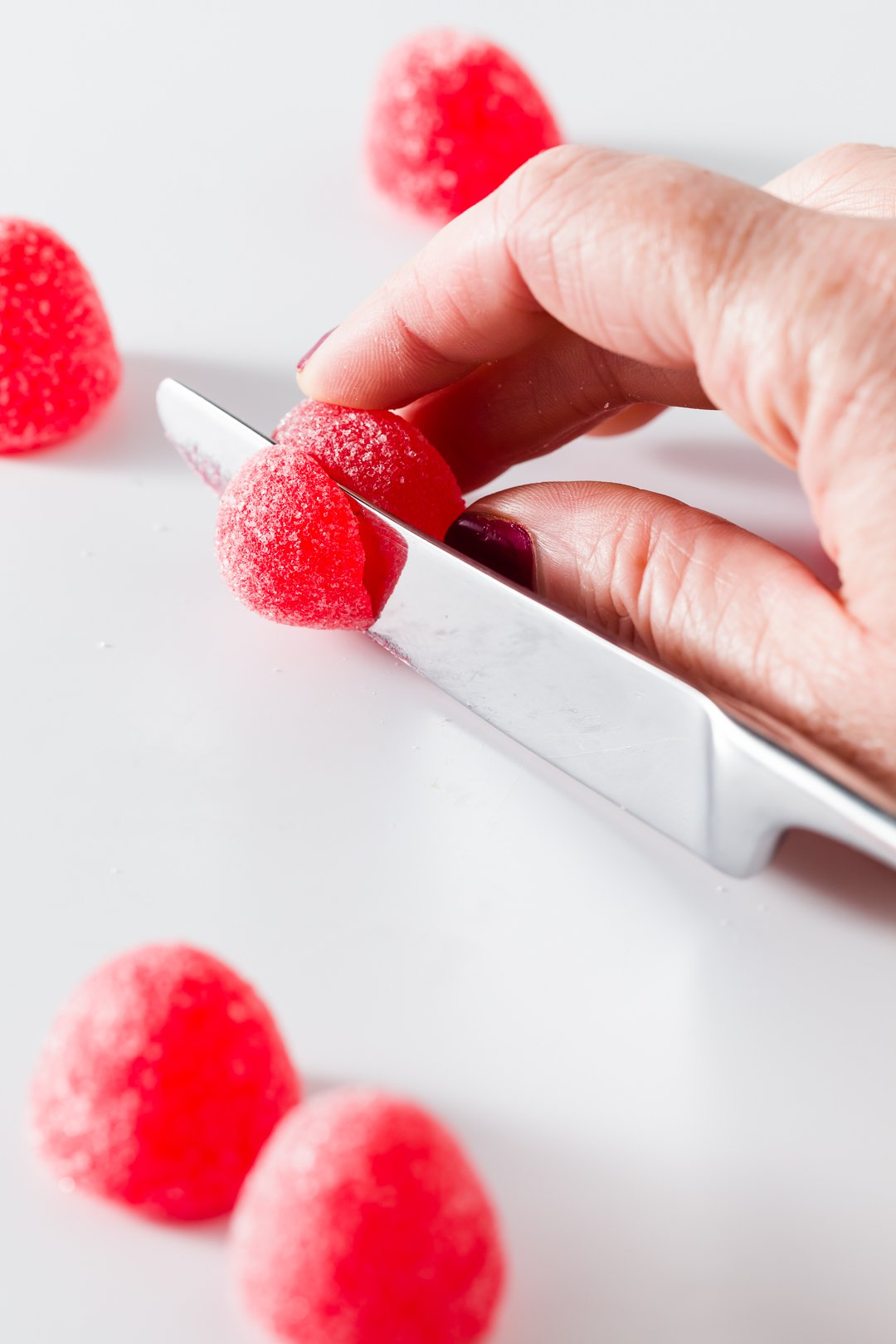 Cutting red gumdrops in half with a knife