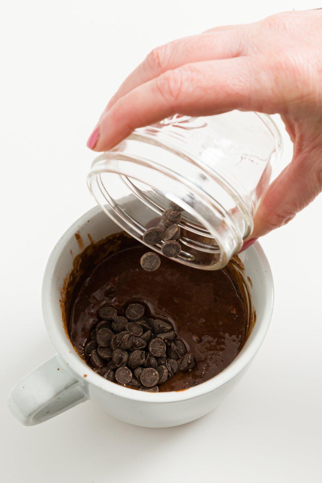 Adding chocolate chips to mug