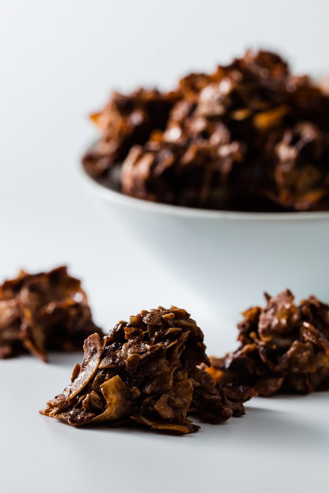 A bowl of chocolate macaroons with some in the front