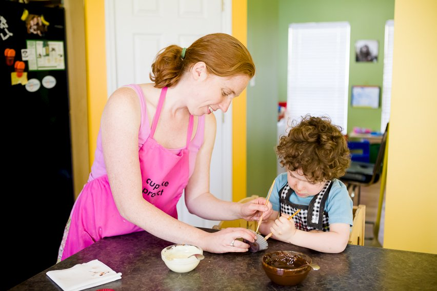 Mother and son paining chocolate cup together