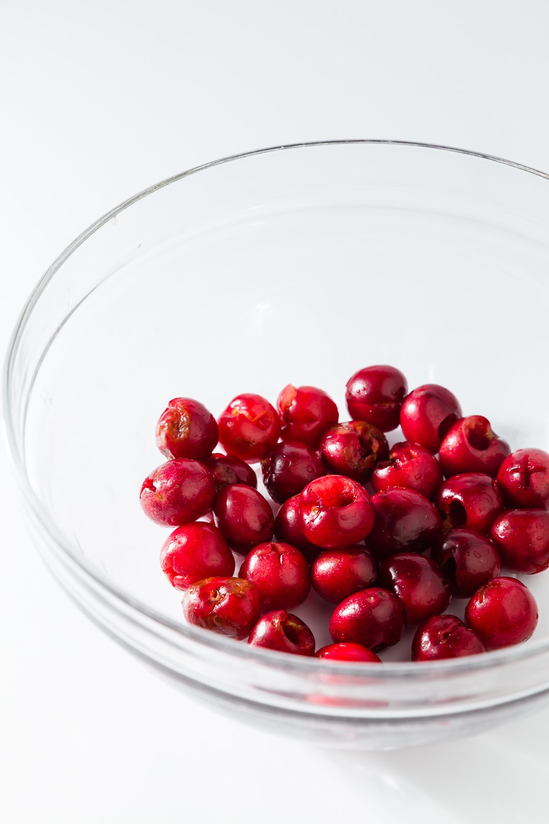 A glass bowl of pitted cherries